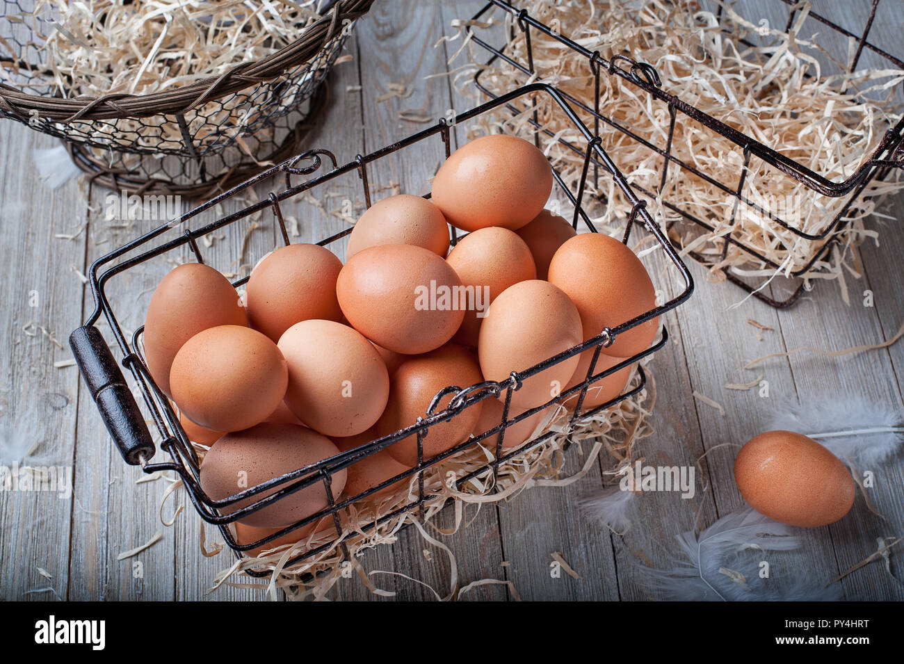 Visual metaphor/proverb: Don't put all of your eggs in one basket with whole eggs. - Stock Image