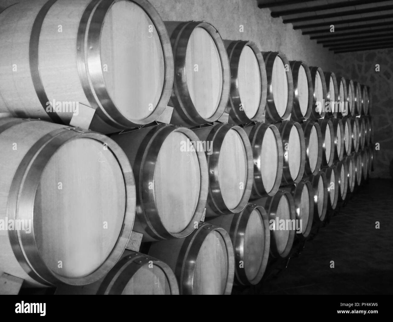 Old wine barrels in a wine cellar.  Stacked up wine bottles in the cellar, dusty but tasty. - Stock Image