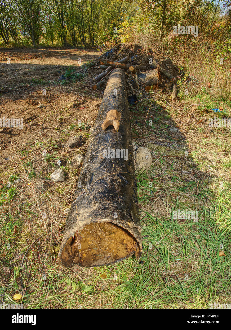 Rusty water pipeline in the trench ground overhead view. Repairing of the water delivery system. Tube at open trench - Stock Image