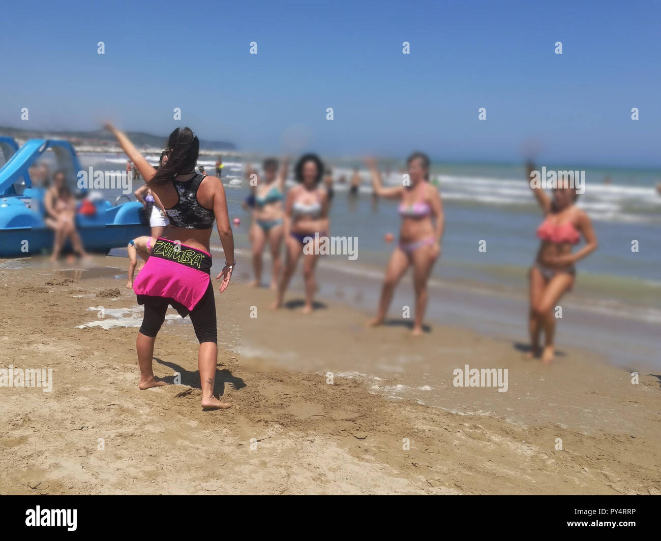 Woman Doing Zoomba Work Out Excercise on the Beach - Stock Image