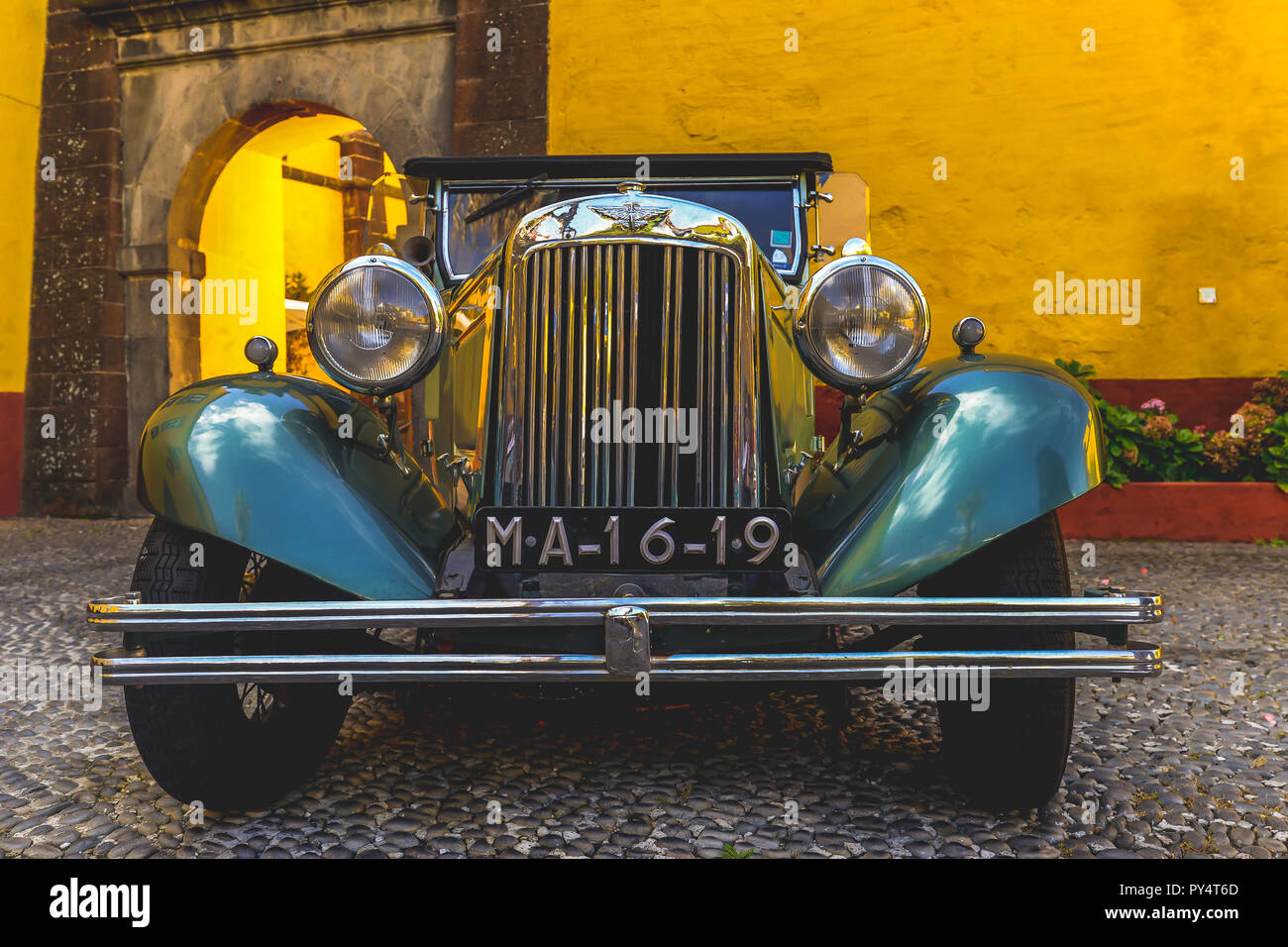 An antique car in a colorful yellow fort in Funchal - Maderia - Portugal - Stock Image