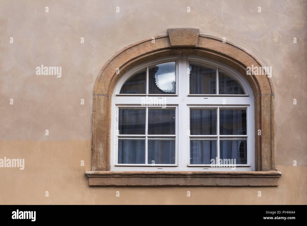 Wall of a house in tones of brown color with a window with stone frame with an arch. White curtains and reflection on the glass. Old city of Prague, C - Stock Image