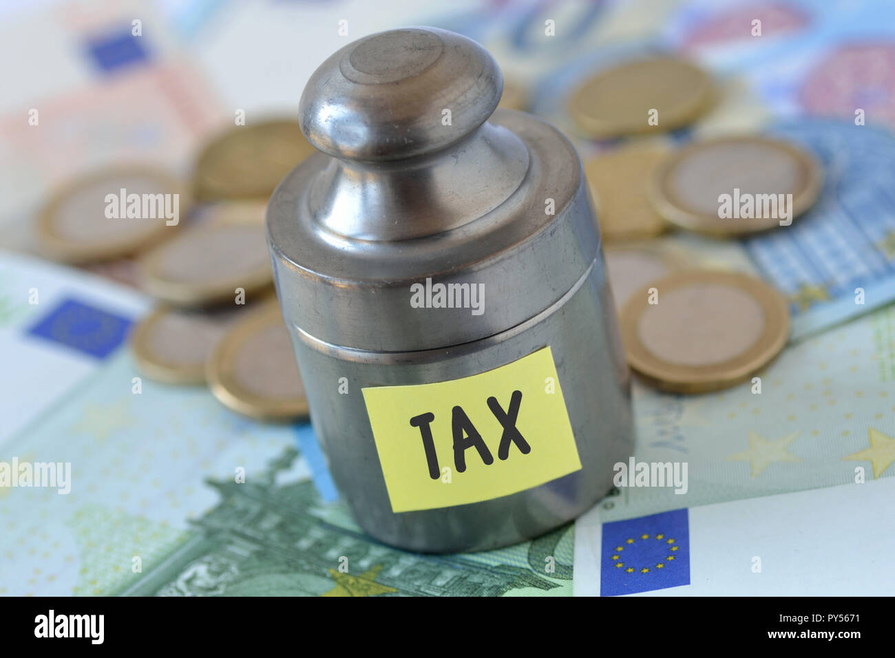 Weight with the word Tax written on paper note on euro banknotes and coins - Finance and taxation concept - Stock Image
