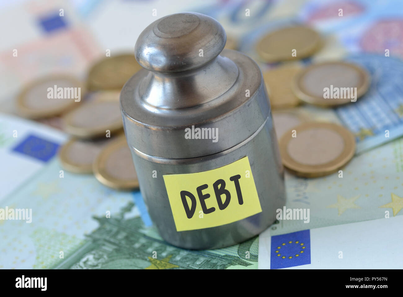 Weight with the word Debt written on paper note on euro banknotes and coins - Debt concept - Stock Image