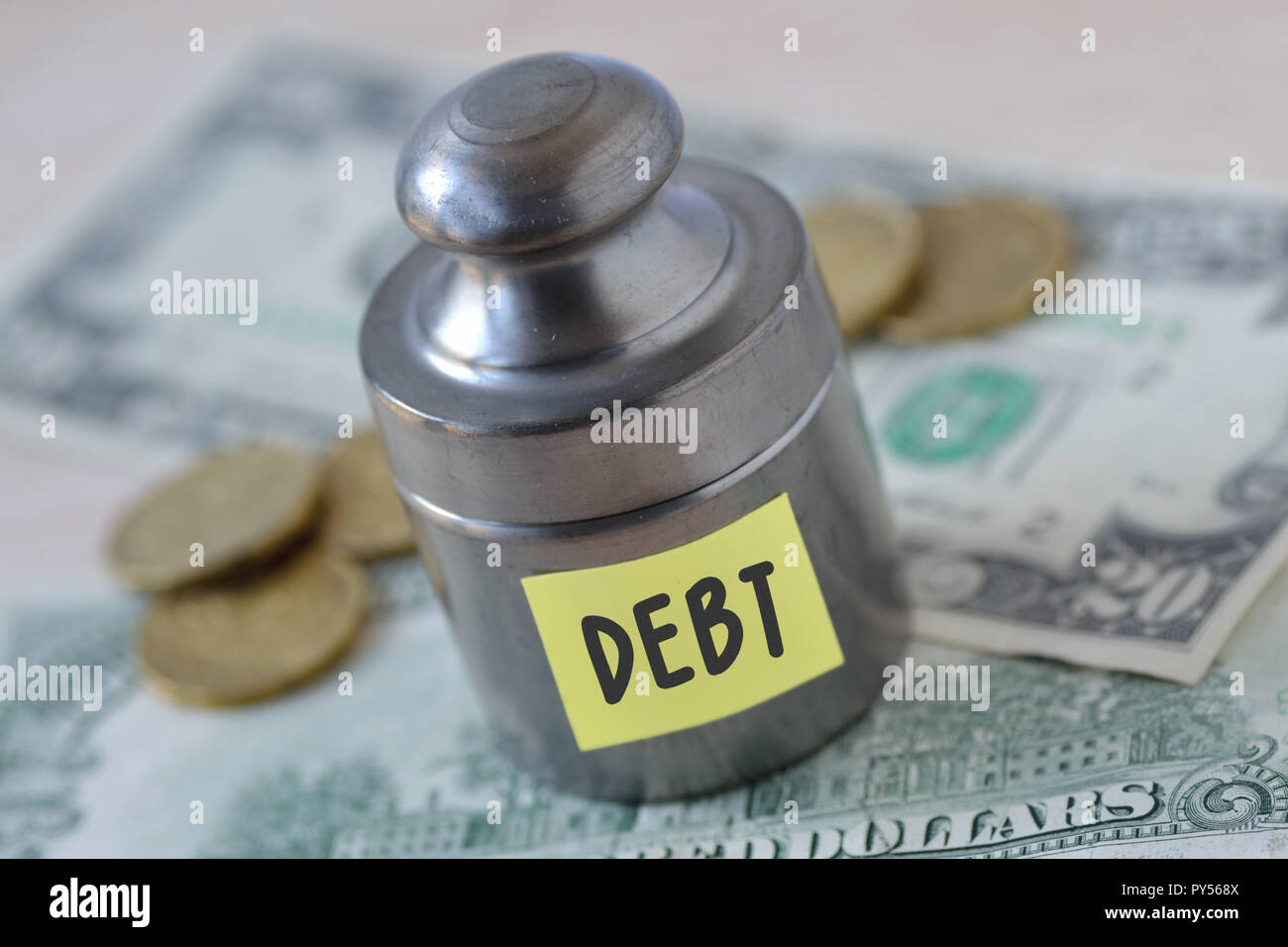 Weight with the word Debt written on paper note on dollar banknotes and coins - Debt concept - Stock Image