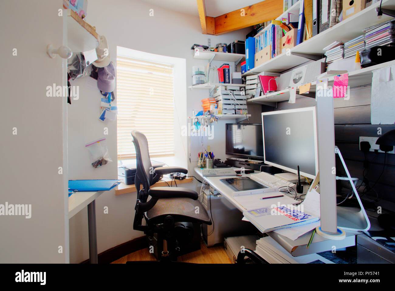 A shot of a messy desk in a home office, the room is small and cluttered, on the desk is three computer monitors and office supplies. - Stock Image