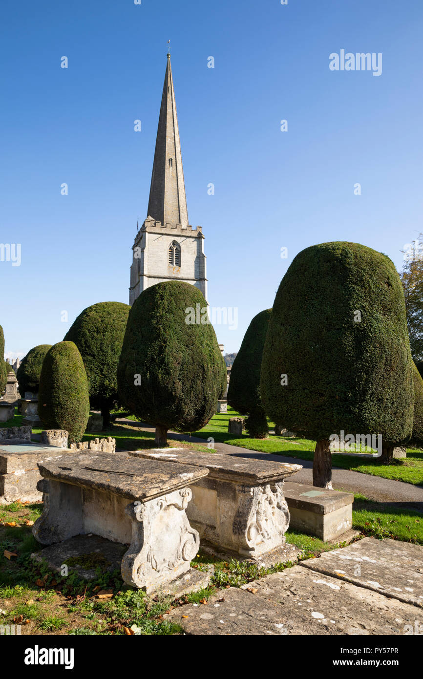 St Mary's parish church with yew trees and chest tombs in the churchyard in afternoon sunshine, Painswick, Cotswolds, Gloucestershire, England, UK - Stock Image