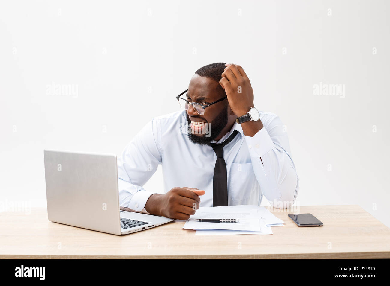Disappointed African businessman is dazed and confused by a mistake in official documents. He feels total disagreement about the deal - Stock Image
