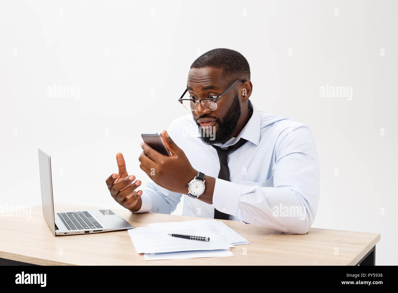 Disappointed African businessman is dazed and confused talking on phone. He feels total disagreement about the deal. - Stock Image