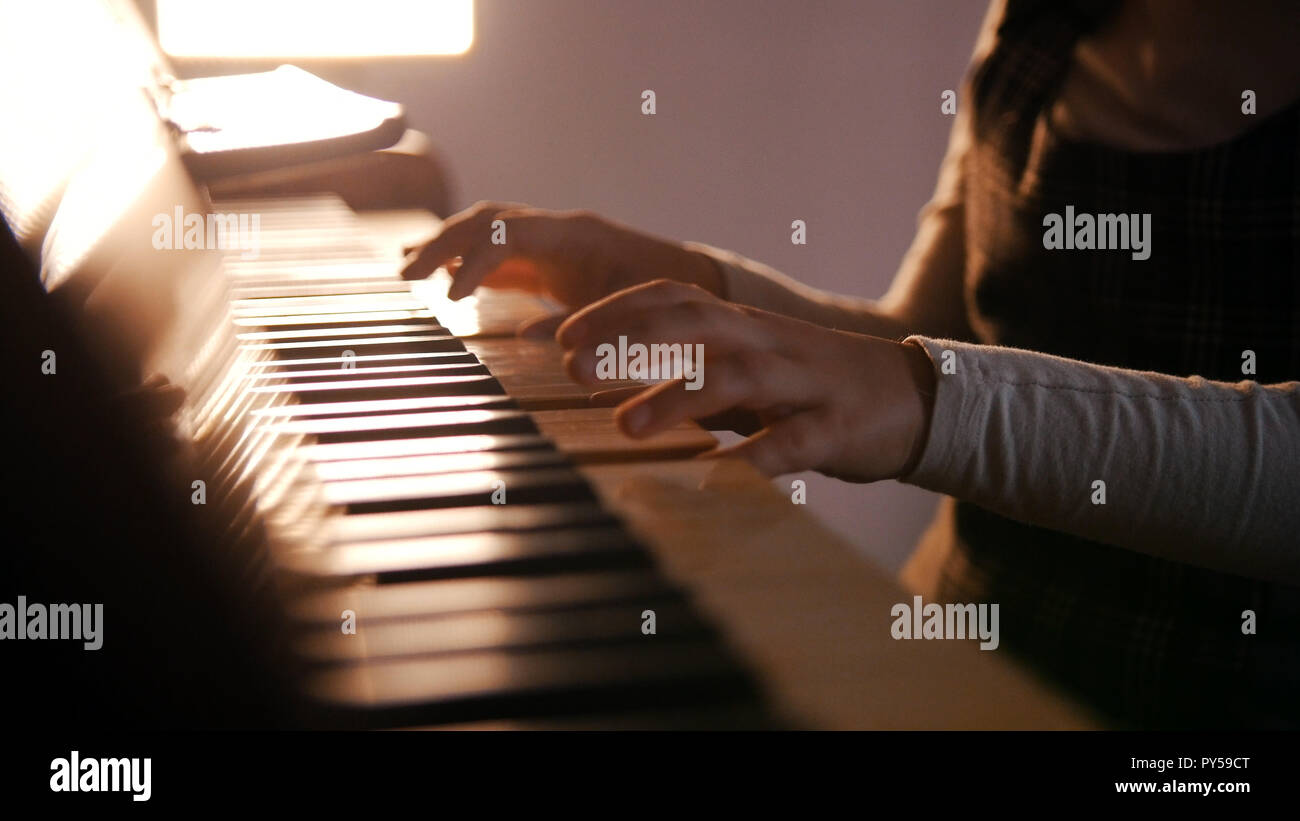 A baby playing piano on music lesson. Beautiful sunlight Stock Photo