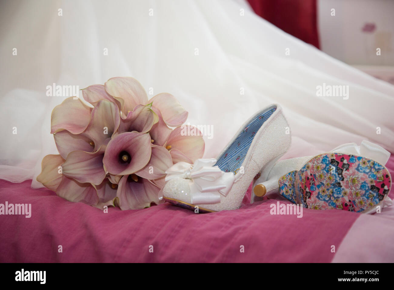 Brides Shoes On The Bed Next To Her Bouquet Of Pink Calla Lilies