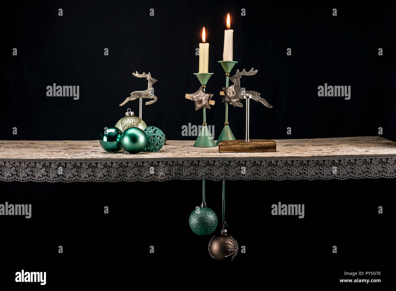 Christmas decoration elements in warm turquoise tones against a dark background. In addition to turquoise, dark brown, wood and old silver create a Ch Stock Photo