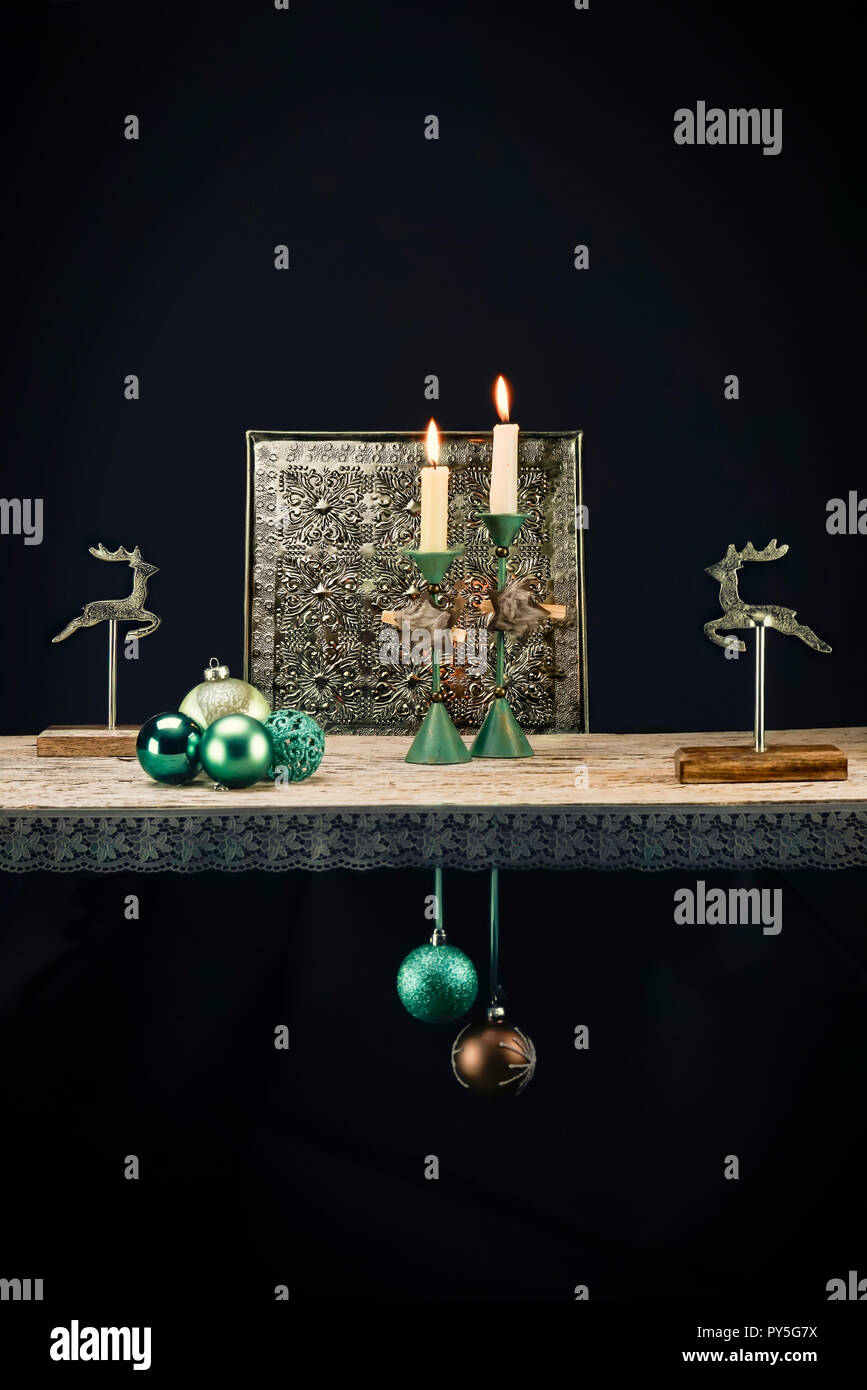 Christmas decoration elements in warm turquoise tones against a dark background. In addition to turquoise, dark brown, wood and old silver create a Ch - Stock Image