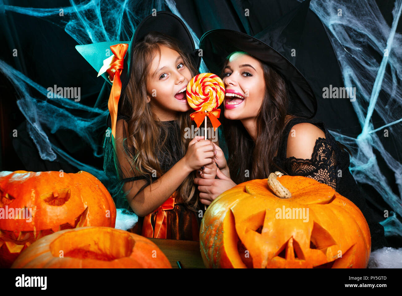 Halloween Concept - beautiful caucasian mother and her daughter in witch costumes celebrating Halloween with Halloween candy and sweet over spider web Stock Photo