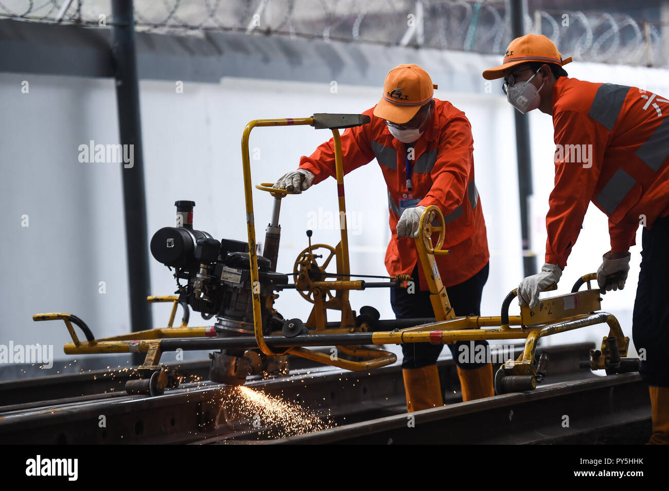 Liupanshui, China's Guizhou Province. 25th Oct, 2018. Two contestants burnish rail during a skill competition in Liupanshui, southwest China's Guizhou Province, Oct. 25, 2018. A total of 30 railway workers participated in the competition. Credit: Tao Liang/Xinhua/Alamy Live News - Stock Image