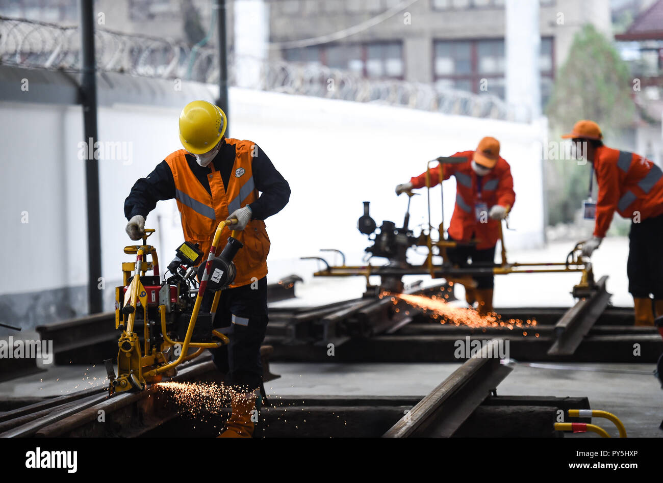 Liupanshui, China's Guizhou Province. 25th Oct, 2018. Contestants burnish rail during a skill competition in Liupanshui, southwest China's Guizhou Province, Oct. 25, 2018. A total of 30 railway workers participated in the competition. Credit: Tao Liang/Xinhua/Alamy Live News - Stock Image