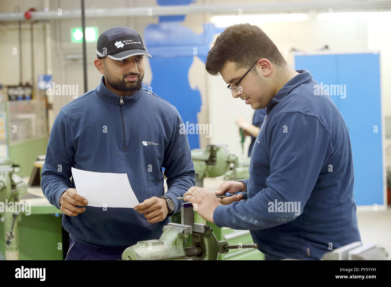 Berlin, Germany. 26th Oct, 2018. At the beginning of a press conference on the campaign 'Training: A question of attitude' at the training facility of Berliner Wasserwerke, trainees converse. The campaign aims to recruit more trainees with a migration history. Credit: Wolfgang Kumm/dpa/Alamy Live News - Stock Image