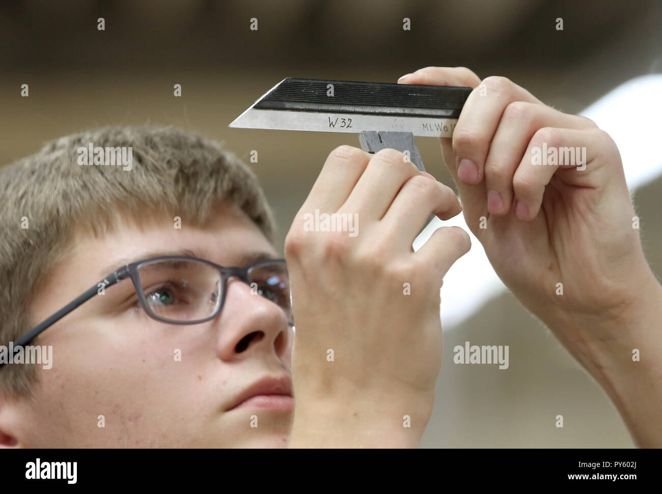 Berlin, Germany. 26th Oct, 2018. At the beginning of a press conference on the 'Training: A Question of Adjustment' campaign, a trainee checks the accuracy of a workpiece at the Berliner Wasserwerke training facility. The campaign aims to recruit more trainees with a migration history. Credit: Wolfgang Kumm/dpa/Alamy Live News - Stock Image