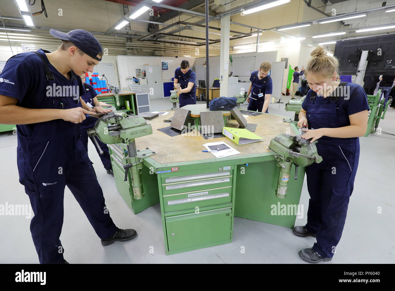 Berlin, Germany. 26th Oct, 2018. At the beginning of a press conference on the campaign 'Training: A question of attitude' at their workbenches, trainees are standing in the training facility of Berliner Wasserwerke. The campaign aims to recruit more trainees with a migration history. Credit: Wolfgang Kumm/dpa/Alamy Live News - Stock Image