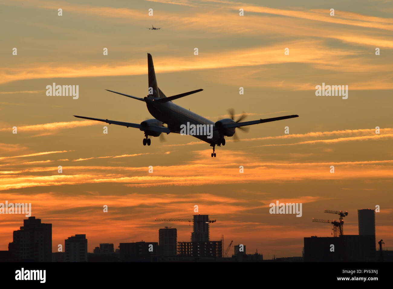 A small turbo-prop passenger plane comes in to land at London City Airport at sunset - Stock Image