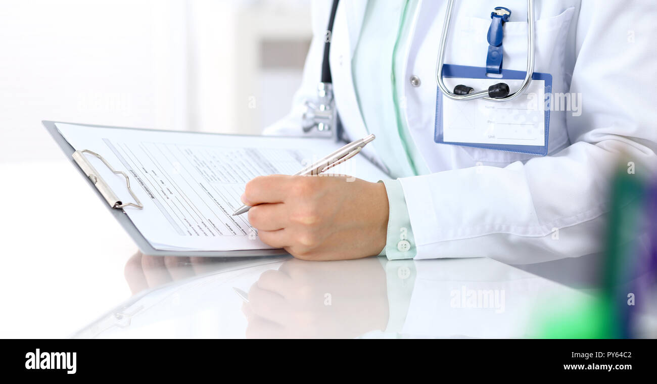 doctor filling up an application form with silver pen ... on medical assistant job application, office assistant job application, restaurant job application, medical center job application,