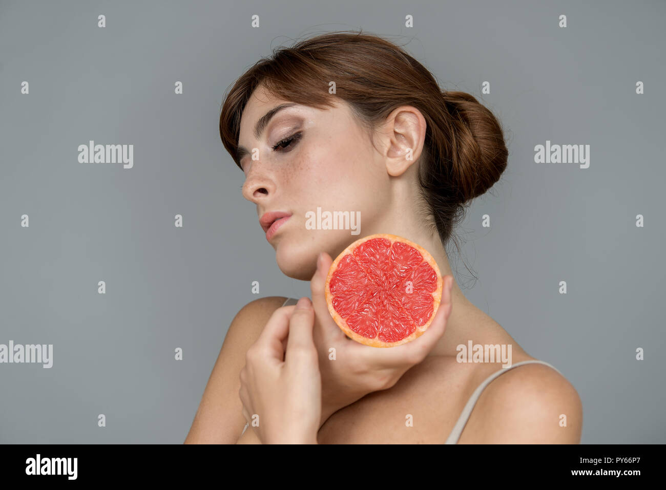 Various expression by young girl with fresh grapefruit   on neutral background - Stock Image