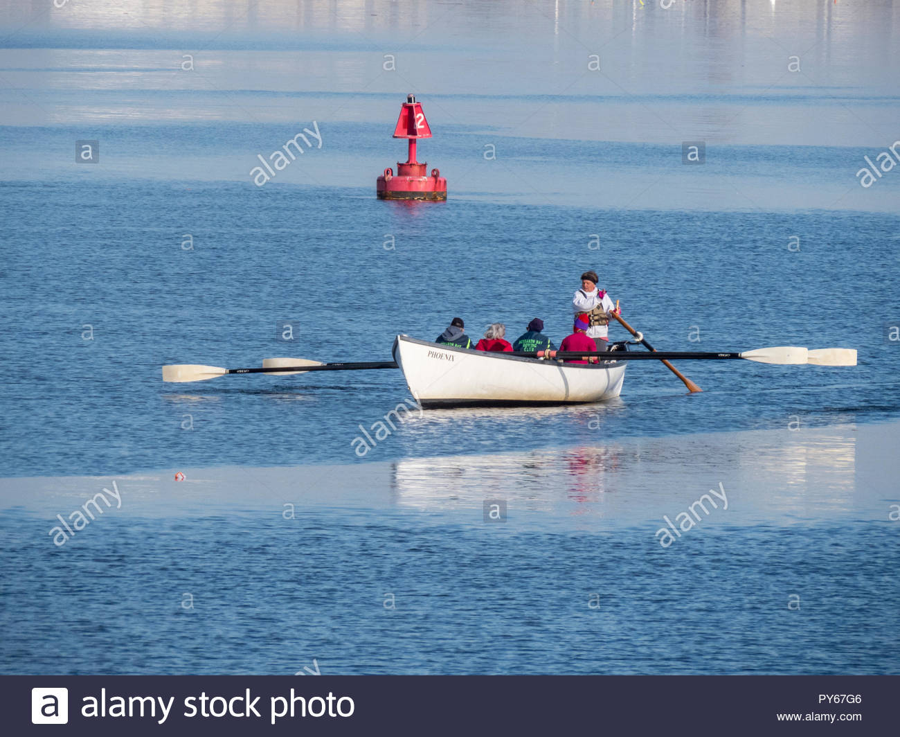 Fairhaven, Massachusetts, USA - March 1, 2018: Members of Buzzards Bay Rowing Club power whaleboat across the Acushnet River on calm day - Stock Image