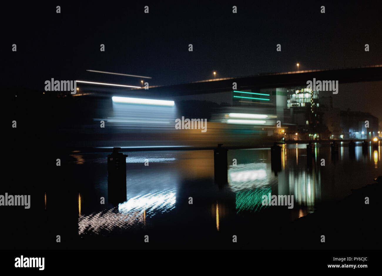 Light trails left by a ship on the canal at night that is heading towards the Olympia bridge Kiel-Holtenau. - Stock Image