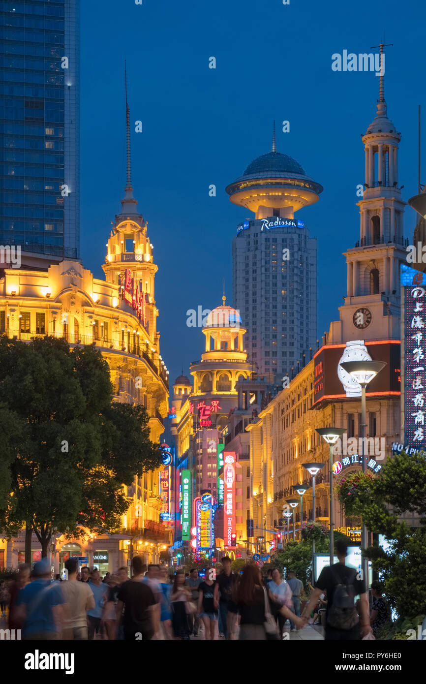 Crowd of People against the Shanghai skyline along a busy crowded Nanjing Road West, Shanghai, China, Asia at night - Stock Image