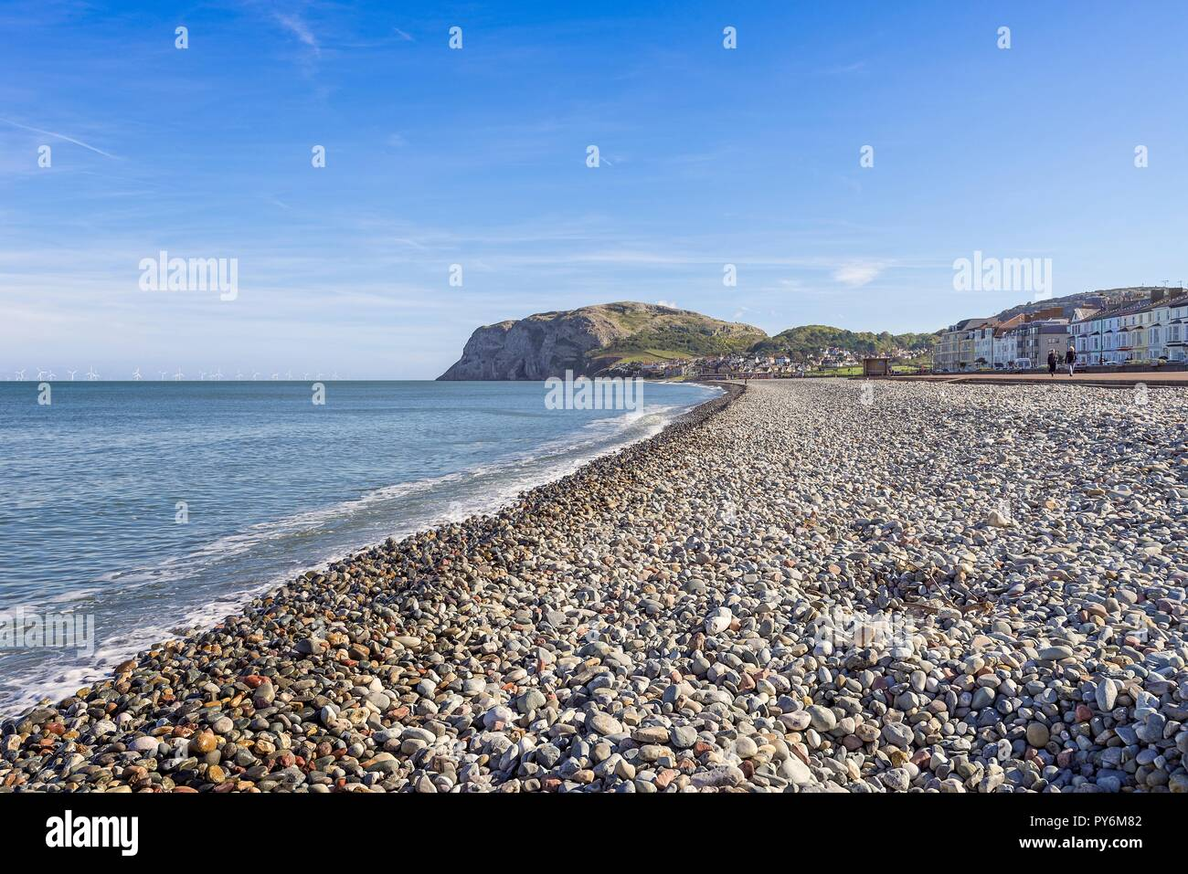 A view of Llandudno's curving shoreline with houses nested by a headland. The Little Orme is in the distance and a blue sky with clouds is above. Stock Photo