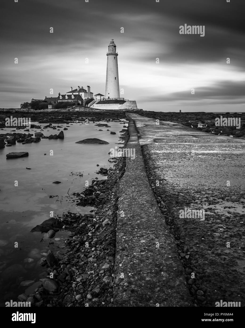 St. Mary's Lighthouse  just north of Whitley Bay on the Northumbrian coast. The small rocky tidal island is linked to the mainland by a short concrete - Stock Image