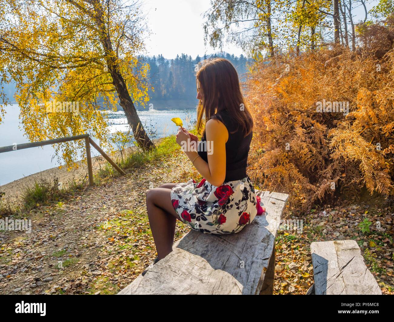 Sitting near lake in countryside young woman is sitting holding one single Autumn leaf in hands nostalgia nostalgic Stock Photo