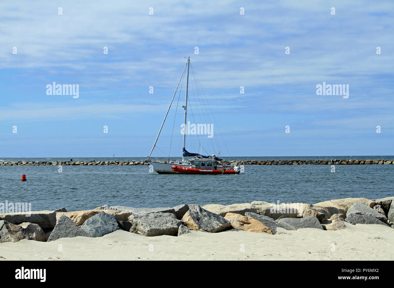 A disabled sailboat being pulled by a TowBoat U.S. through the jetty marking the entrance to Sesuit Harbor on Cape Cod in East Dennis, Massachusetts - Stock Image