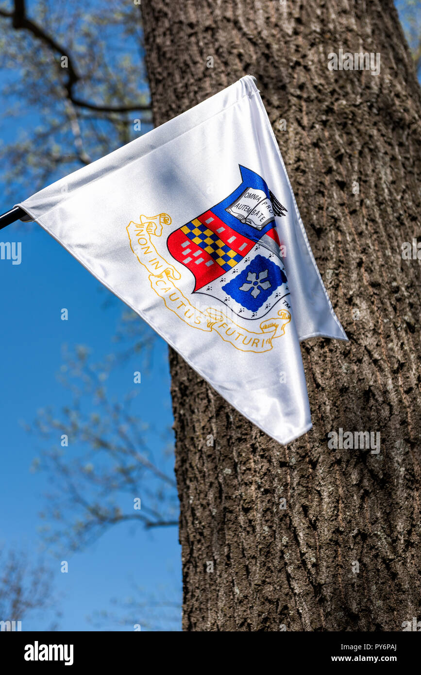 Lexington, USA - April 18, 2018: Washington and Lee University white flag in Virginia closeup isolated against blue sky with sign motto for Non incaut - Stock Image