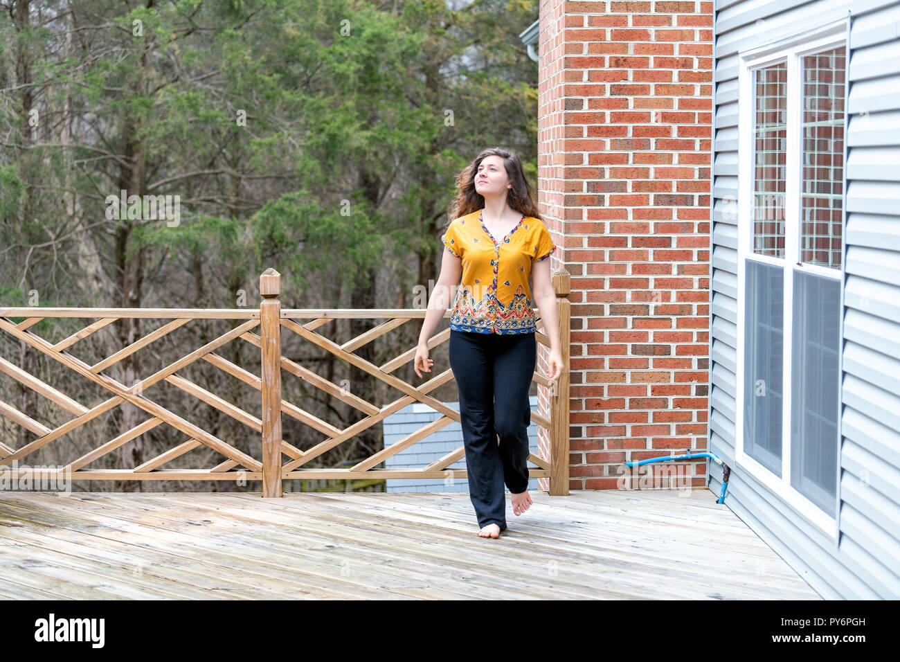 One young woman walking outside, outdoors barefoot on wooden house, home deck, looking up, homeowner at backyard, front yard - Stock Image