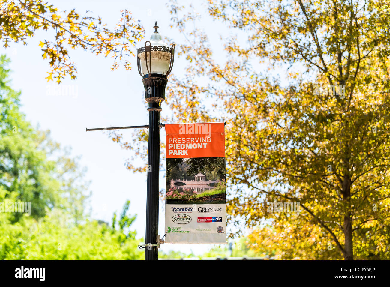 Atlanta, USA - April 20, 2018: Piedmont Park in Georgia capital urban city downtown, sign for preserving, conservancy on lamp lantern post pole - Stock Image