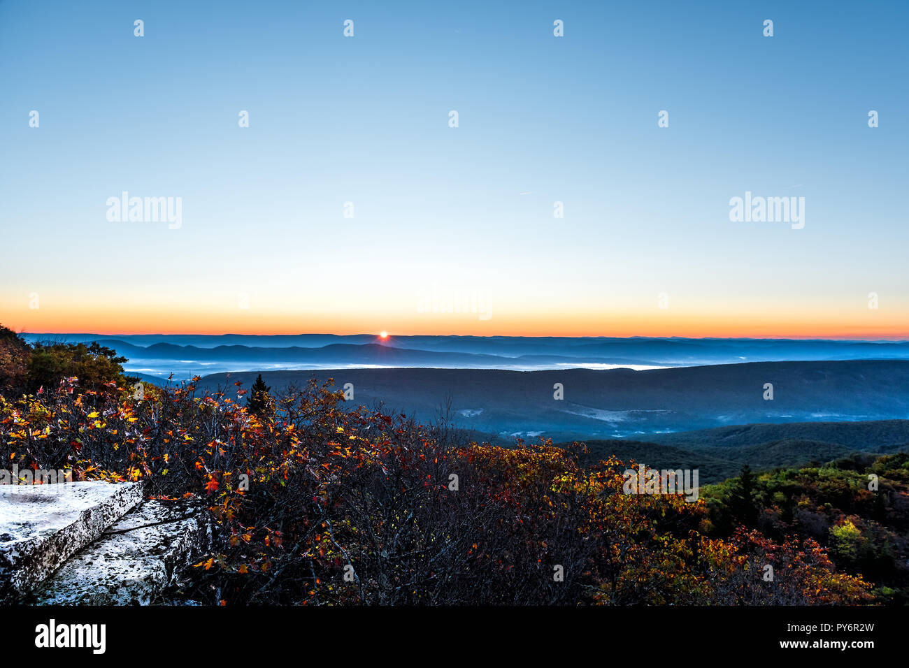 Bear rocks overlook sunrise, sunburst, sunrays, rays, sun behind mountains in autumn with rocky landscape in Dolly Sods, West Virginia with orange, ye Stock Photo