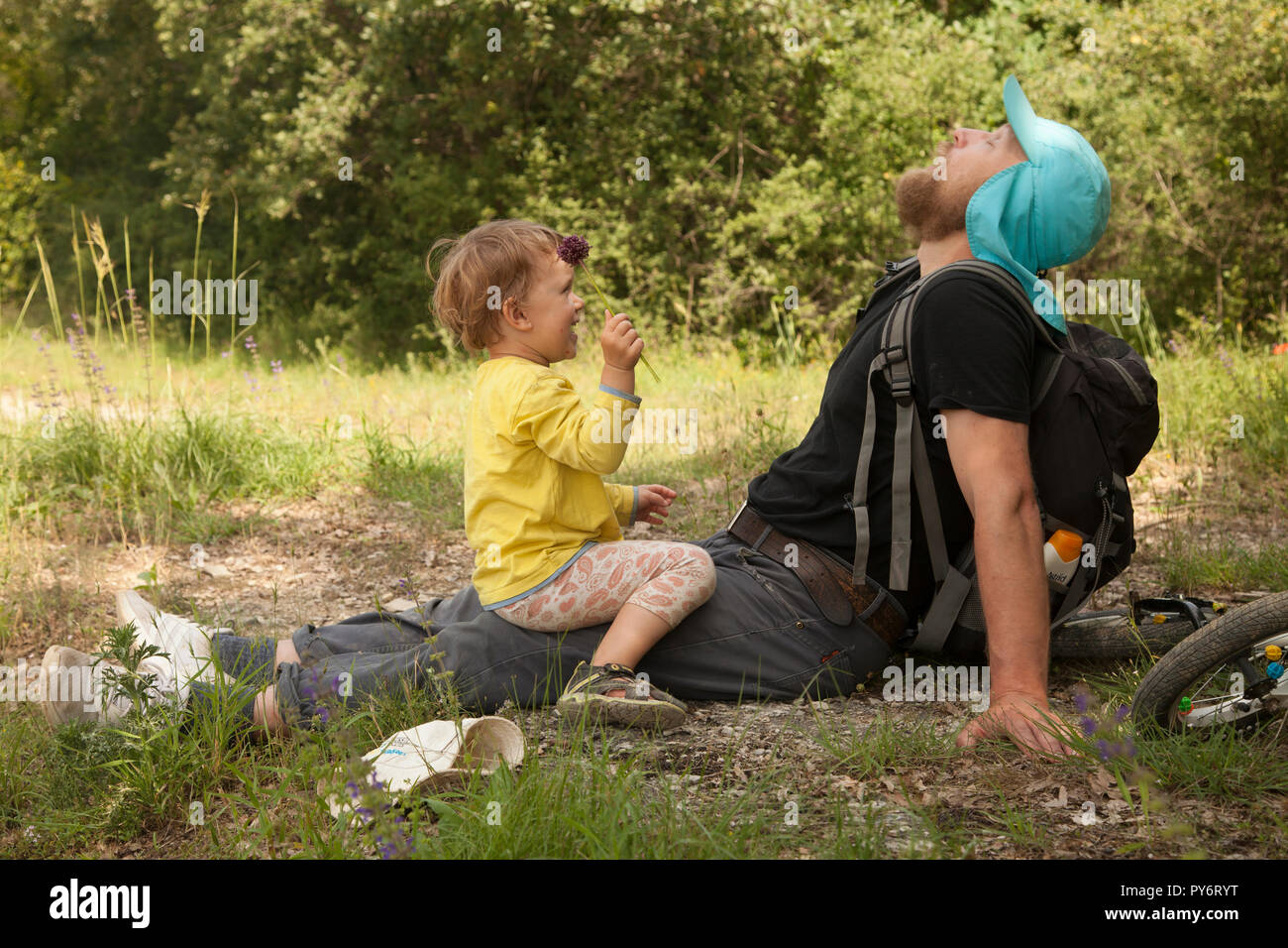 Little girl with her father sniffing a flower and smiling laughing out loud in summer greenery of Croatian nature. - Stock Image
