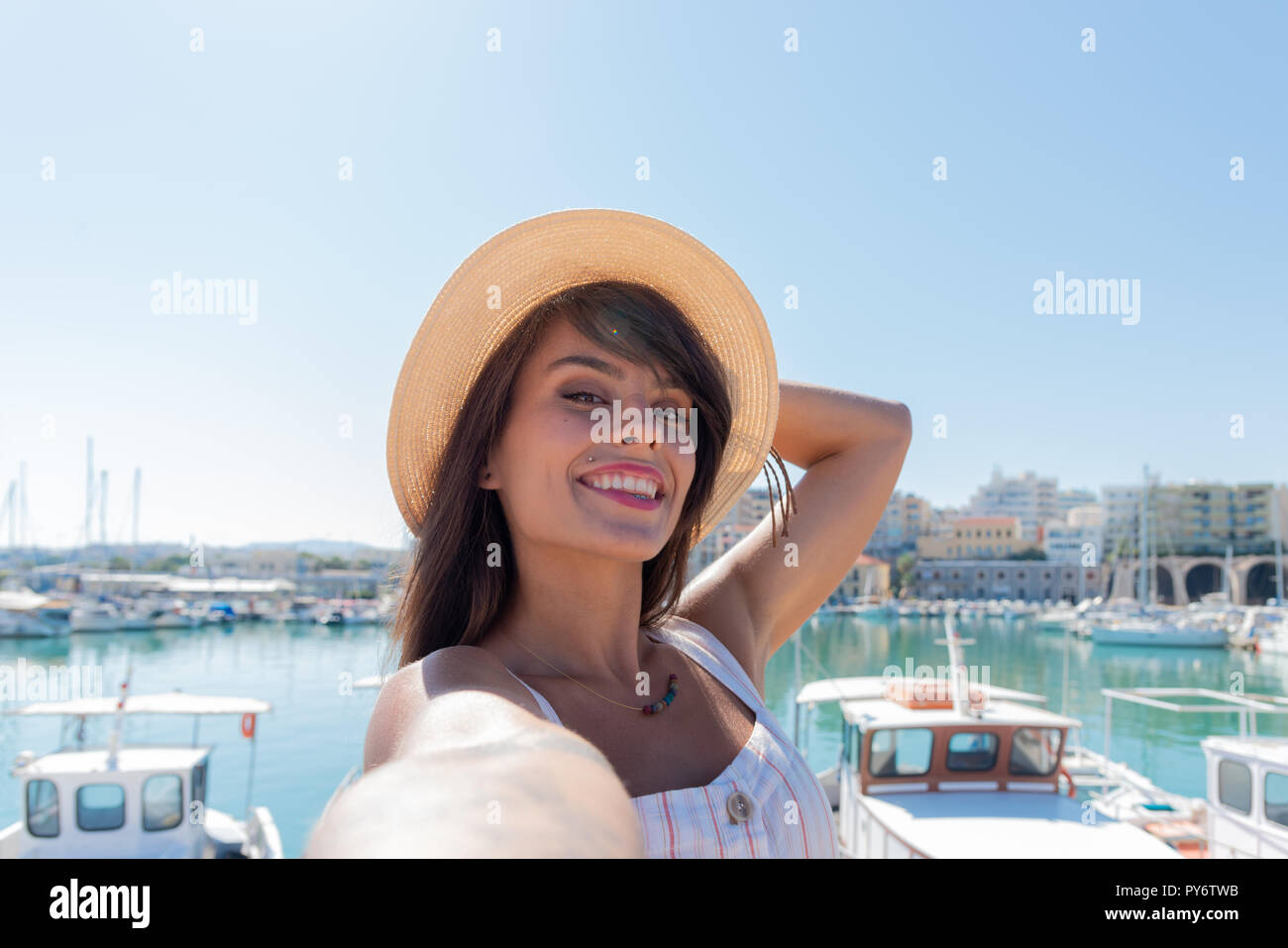 Traveling tourist woman on vacation in Heraklion Crete walking at the port. Lovely elegant girl takes selfies visiting the famous Mediterranean Veneti - Stock Image