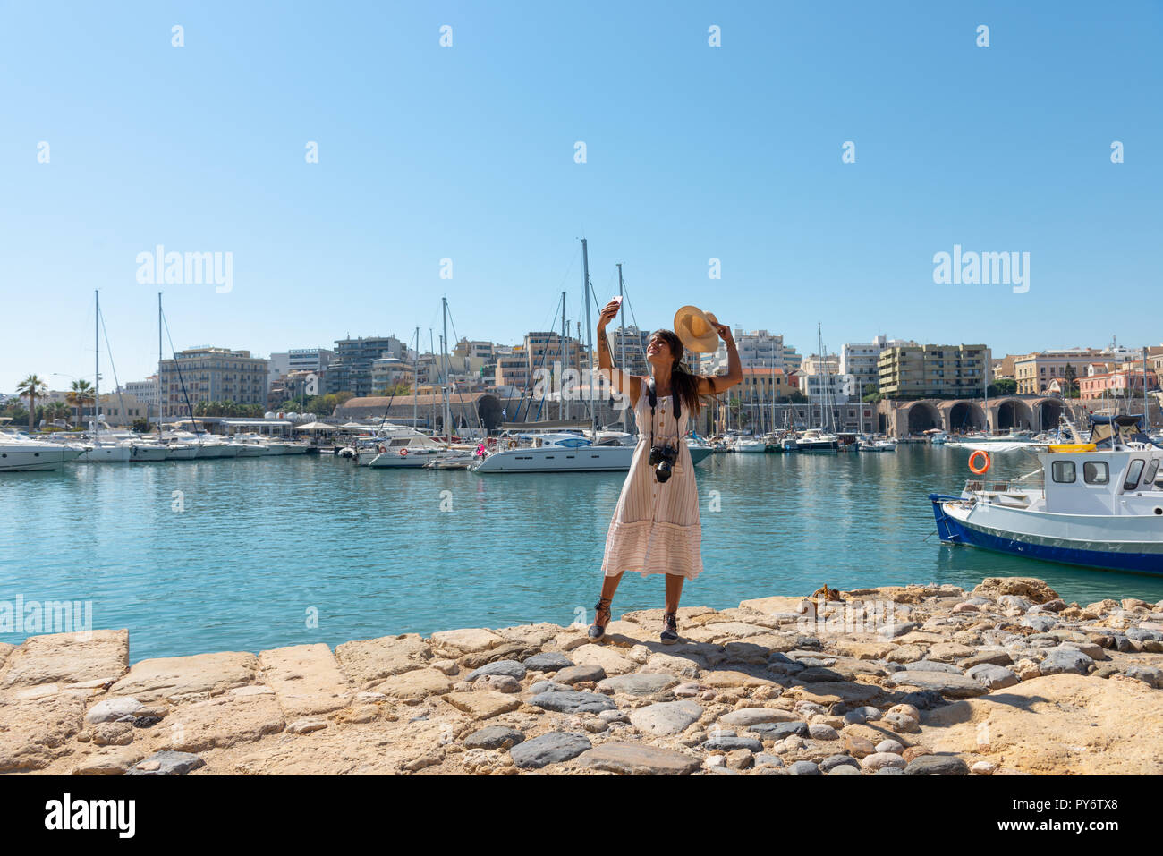 Traveling tourist woman on vacation in Heraklion Crete walking at the port. Lovely elegant girl in beige dress visiting the famous Mediterranean Venet - Stock Image