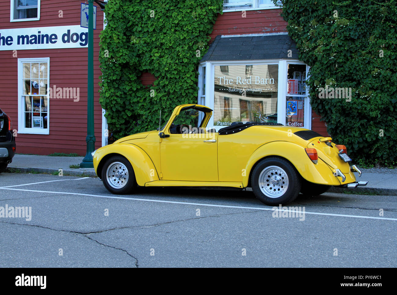 A beautifully restored yellow convertible Volkswagen beetle parked on a side street in Camden, Maine, in front of some shops Stock Photo