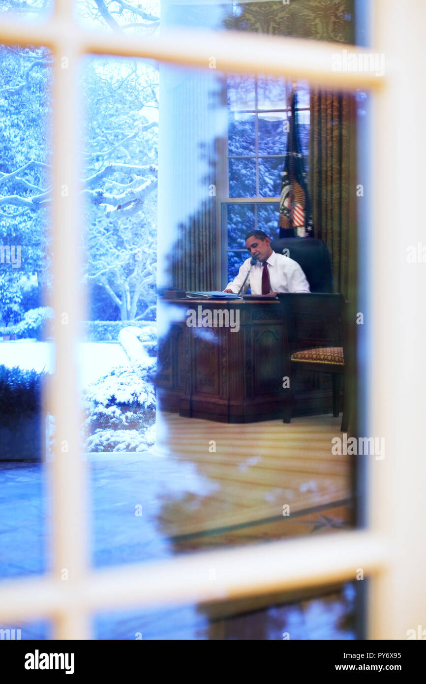 President Barack Obama talks on the phone in the Oval Office 1/27/09. Official White House Photo by Pete Souza Stock Photo