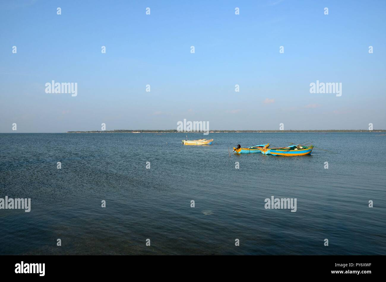 Several blue and yellow boats moored anchored in waters of Jaffna Sri Lanka Stock Photo