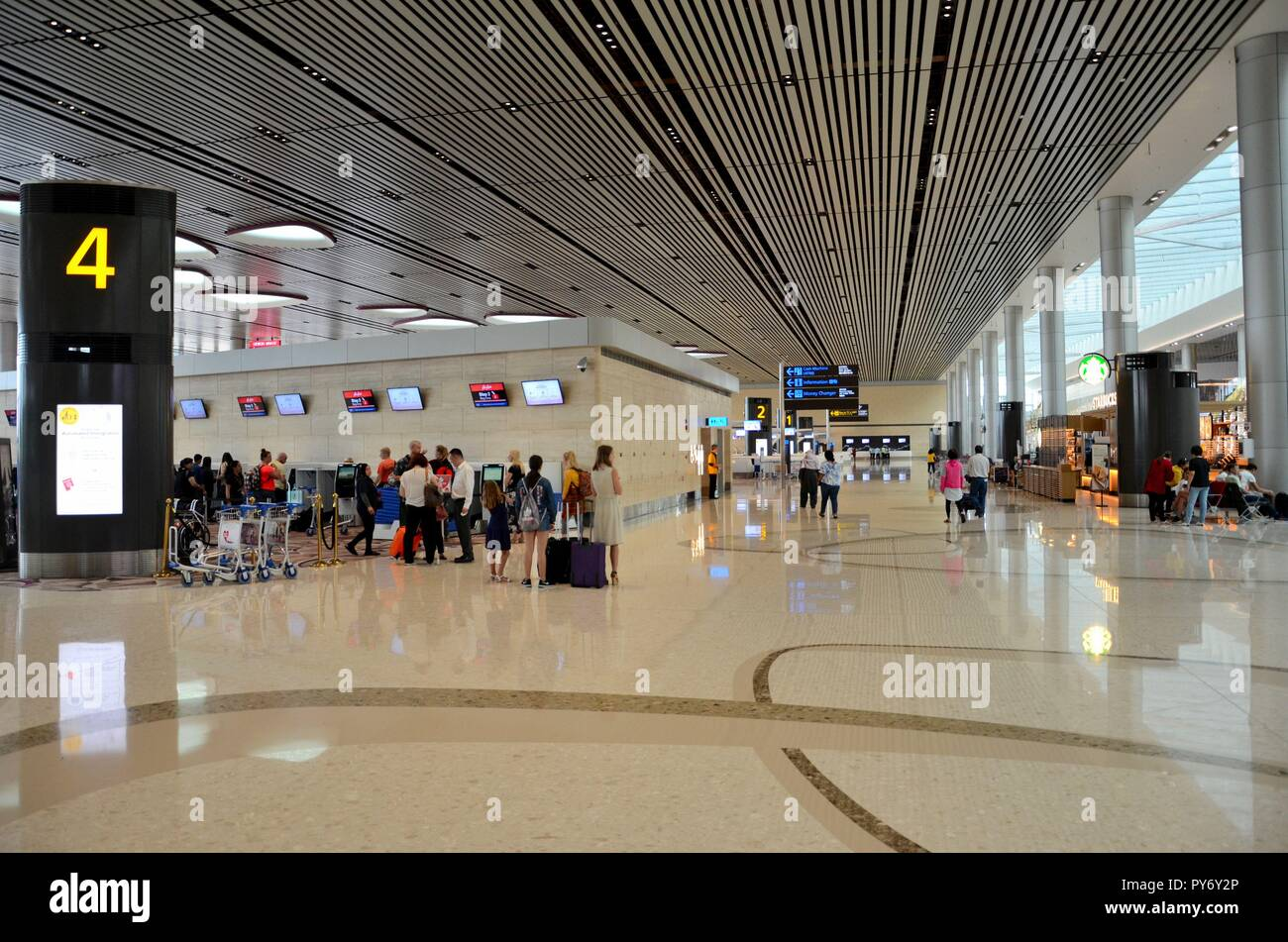 Passengers line up at self check in counters at Singapore Changi airport terminal 4 departures area - Stock Image