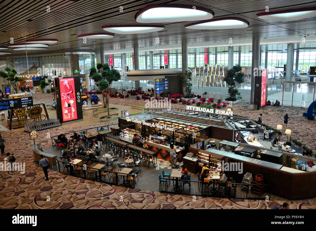 Travellers at cafe inside new terminal four at Singapore Changi Airport - Stock Image