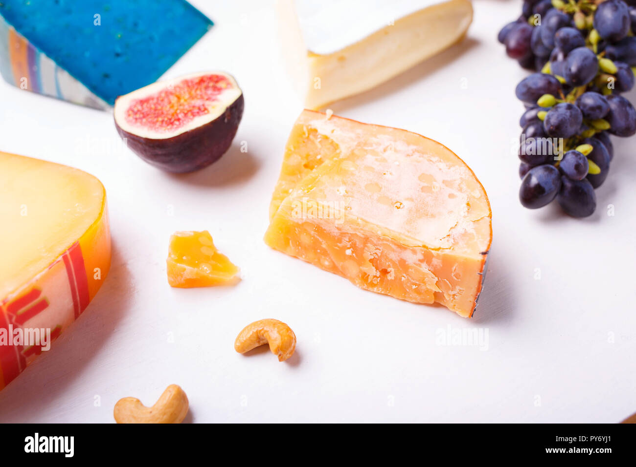 Variety of different cheese with nuts and grapes on the table. Top view image of soft and hard cheeses Stock Photo