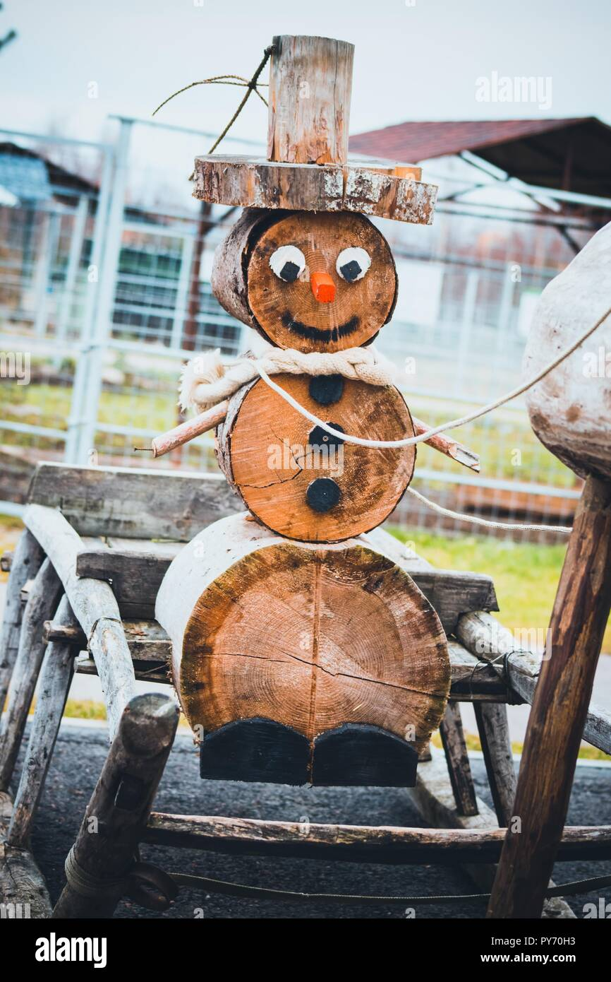 a beautiful snowman made of wood sits in a new years sleigh sleds are harvested by a deer they bring christmas to us