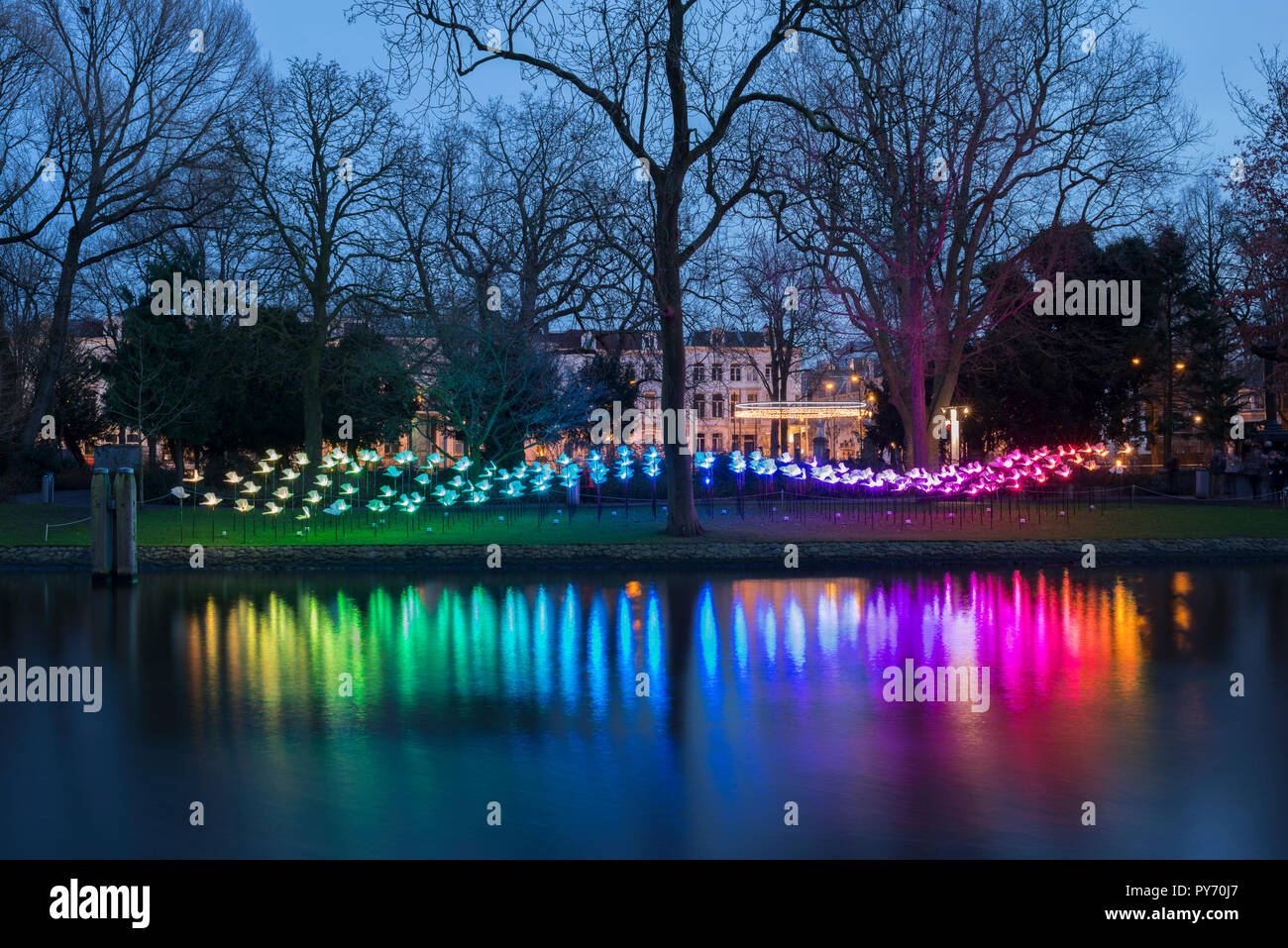 Colorful night in Amsterdam, Wertheimpark during the Amsterdam Light Festival with the artwork On the Wings of Freedom of Aether & Hemera. Stock Photo