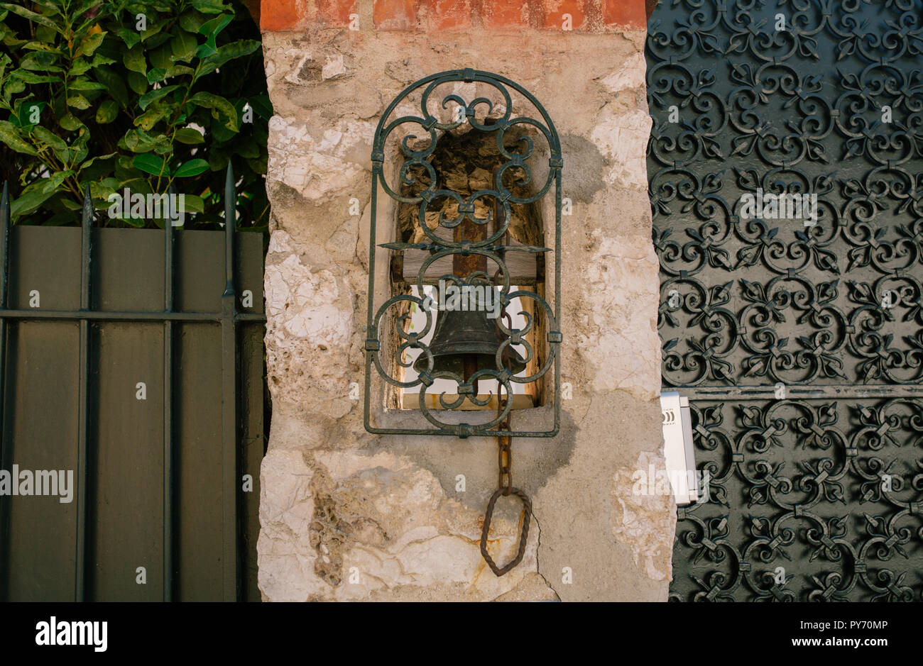 Vintage bell on the wall in the southern European city Stock Photo