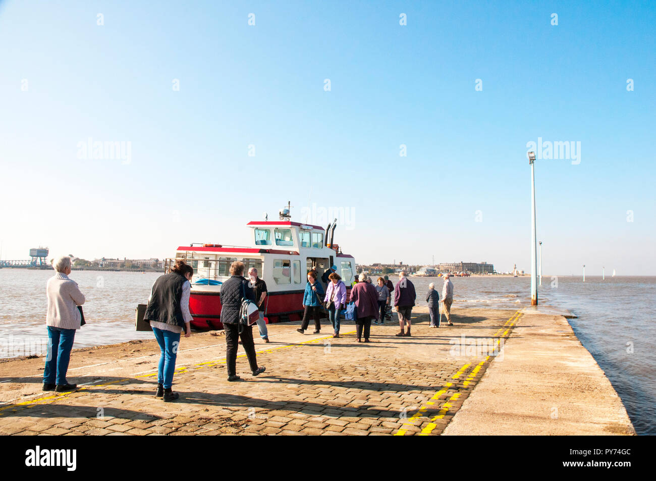 People disembarking whilst others wait to embark on the Fleetwood to Knot End on Sea ferry on Knott End slipway. Lancashire England UK - Stock Image